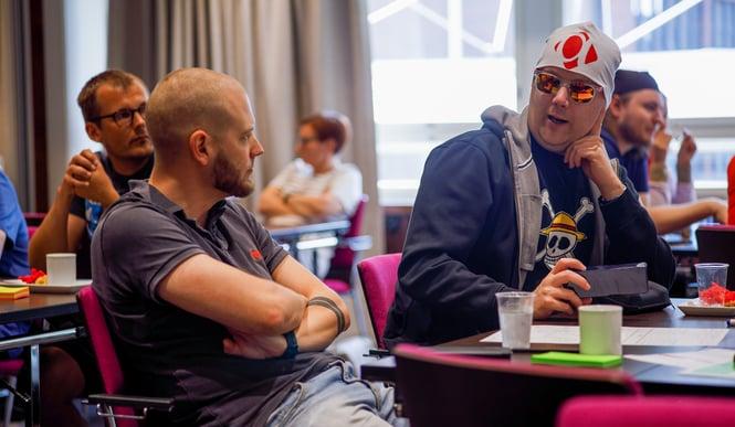 Alfamen työntekijöitä pöydän ääressä juttelemassa.